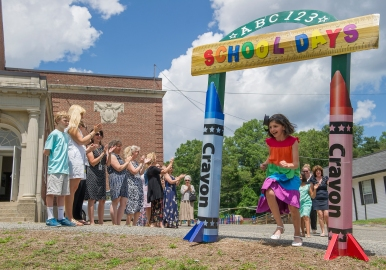 AMANDA SABGA/PHOTO Second grade graduate Kara Stefani runs through the archway in procession as Shawsheen Elementary School celebrates its final assembly, before closing its doors for good, on June 22, 2015.