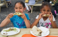 AMANDA SABGA/ STAFF PHOTO Brielle Beers, 7, and her cousin Ava Pichardo, 7, enjoy food from CocoRays a the Lawrence Food Truck Park opening on June 25, 2015.