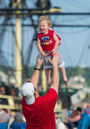 AMANDA SABGA/ Staff photo Salem native Sean Russell tosses his son Stephen in the air as Salem celebrates Independence Day with festivities and fireworks at the Salem Maritime National Historic Site on Derby Wharf. 7/4/15