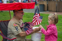 AMANDA SABGA/ Staff photo Autumn Adams, 5, gets an american flag from Veteran Roger Leger as Salem celebrates Independence Day with festivities and fireworks at the Salem Maritime National Historic Site on Derby Wharf. 7/4/15